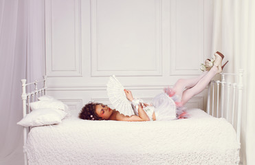 Wedding dress. Young beautiful girl in a white wedding dress on a white bed