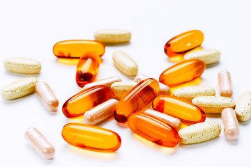 Biological additives to food, vitamins for a healthy lifestyle, capsules an omega 3 with cod-liver oil, transparent orange color an embankment on a light background close up