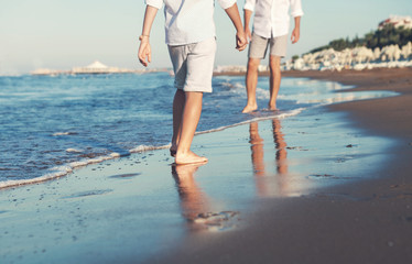 Son legs go to his father on the sea surf line close up image