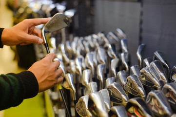 Foto op Aluminium Golf Person holding with hand golf club in a Golf Shop