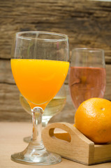 Glass of freshly pressed orange juice with on wooden table