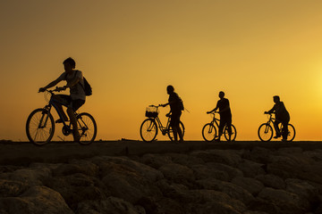 Silhouette of people riding bicycle at Bali beach during beautiful sunrise.