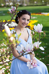 Young smiling girl in evening dress with magnolia
