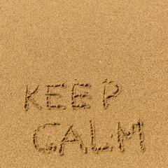 Keep calm - text written on sandy beach. Background, texture of the sand..