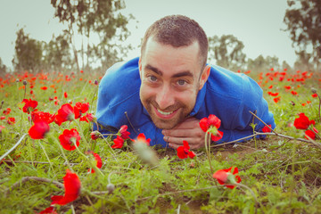 Young man lying on the grass in a field of red poppies and smiling at the camera