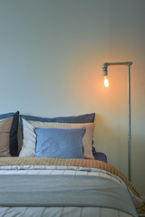 Industrial style reading lamp and blue pillows on modern style bedding