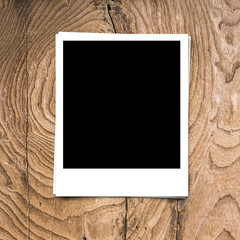 blank photo frame on brown wood background texture