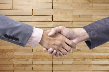 Business handshake on wood background