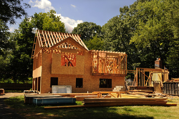 A residential home under construction mid framing and sheathing