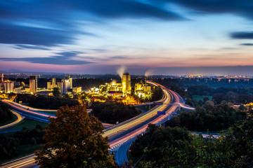 Leuchtspuren von Autos auf der Autobahn A60 bei Mainz an einer Fabrik