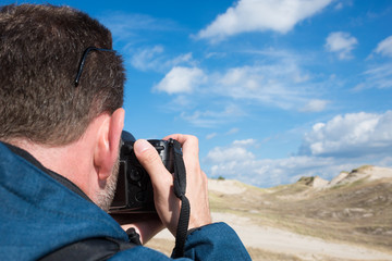 Rear view of a man photographying landscape with digital camera