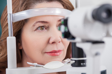 Cheerful lady having eye examination in oculist office Fototapete