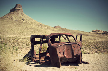 rusty car wreck in desert, vintage filtered style, Route 66, Arizona, USA