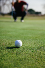 Golf ball with unfocused golfer crouched in the background
