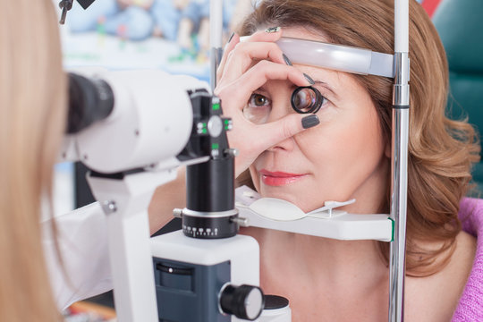Professional female ophthalmologist is checking human eyes
