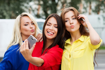 Three beautiful young women posing and grimacing while taking a