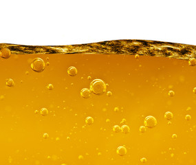 Wave from a yellow liquid with air bubbles on white background