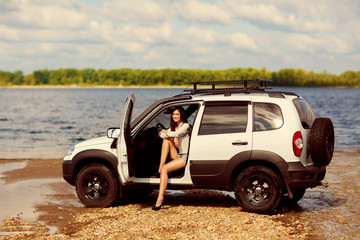beautiful girl and the car near the river