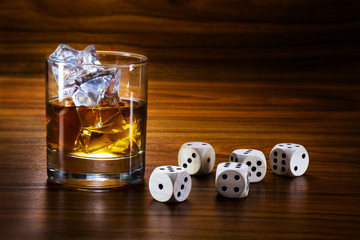 whiskey with ice and dice on a warm toned wooden table, concept