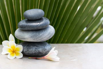Pyramid of stones and plumeria flowers