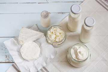 Dairy products. Milk in glass bottle, yogurt, sour milk cheese, sour cream in glass jar, camembert, brie on light blue wooden table