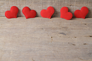 Valentines day background with red hearts on wooden background.