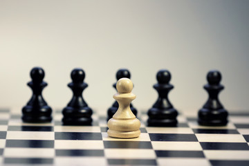 figure white against the black pawn on the chessboard