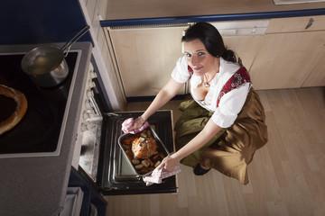 Frau holt Schweinshaxe aus dem Rohr
