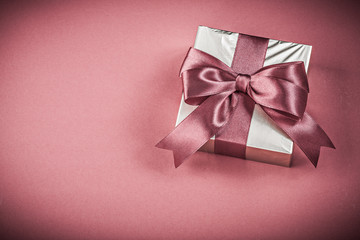 Present box on red background holidays concept