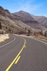 Lonely Two Lane Divided Highway Cuts Through Dry Mountains