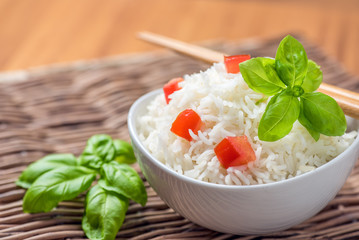 Cooked basmati rice in a bowl with chipsticks, tomato and basil