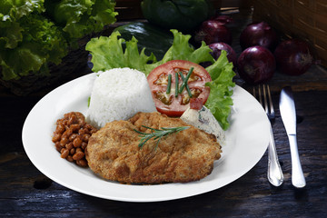meal with escalope rice, beans and salad on a wooden table