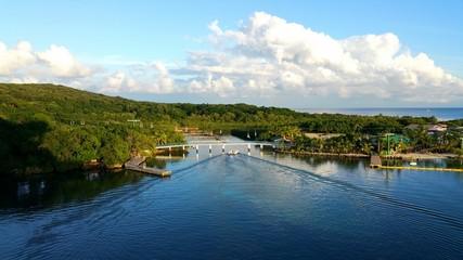 A small boat creates symmetrical ripples as it travels through a bridge.