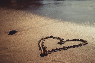 Heart drawn on sand sea beach