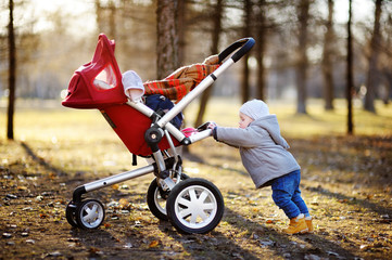 Toddler boy playing with his stroller at the warm spring day