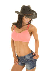 Cowgirl in denim shorts and pink sports bra hand in belt loop