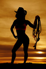 Silhouette of cowgirl hold rope