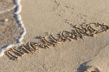 Inscription Thailand on sandy beach with wave's foam