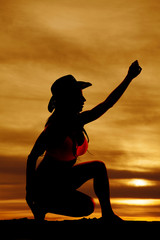 Silhouette of cowgirl reaching up