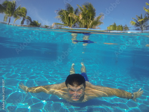 Man swimming underwater in a pool that shows both below for Pool man show