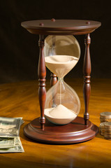 Large hour glass surrounded by paper cash money and coins on a wooden table representing time running out,  investing time, deadlines, stress, financial planning and the wisdom that comes with time.