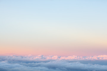 Background: above the clouds on beautiful sunset sky