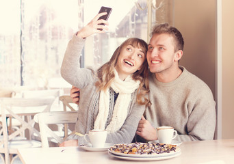 Happy young couple relaxing in a cafe with pizza and coffee