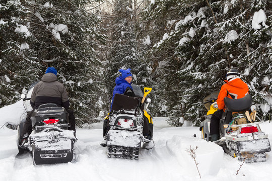 Three friends on snowmobiles.