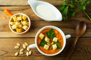 Roasted pumpkin squash cream soup with parsley and croutons in the white bowl on the dark wooden background, top view