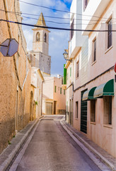 Wall Mural - Narrow street with an church spire at background