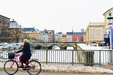 Girl on bicycle passing by the bridge in winter Copenhagen