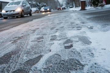 Fußspuren im Schnee und Autos