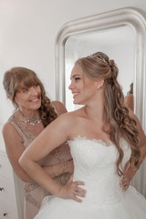 bride and mother dressing on wedding day.