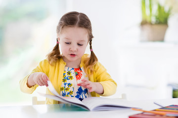 Little girl painting and writing